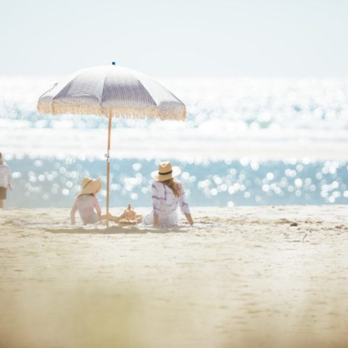 burleigh-currumbin-family-with-mother-and-daughter-under-umbrella-on-beach