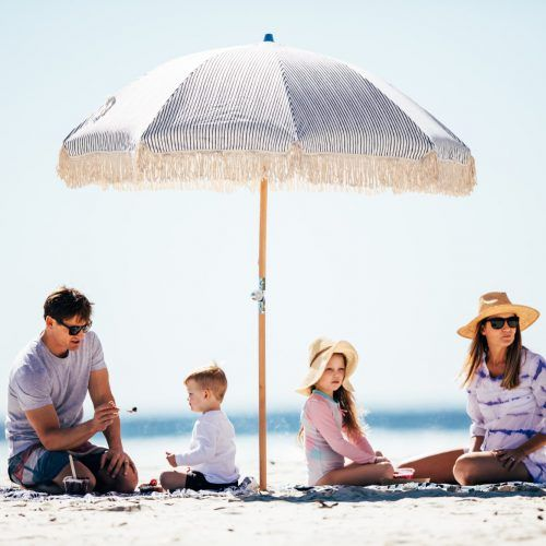 gc-tourism-burleigh-currumbin-family-on-rug-under-umbrella-on-beach
